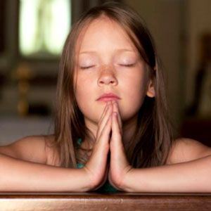 Mamãe ensinando criança a rezar